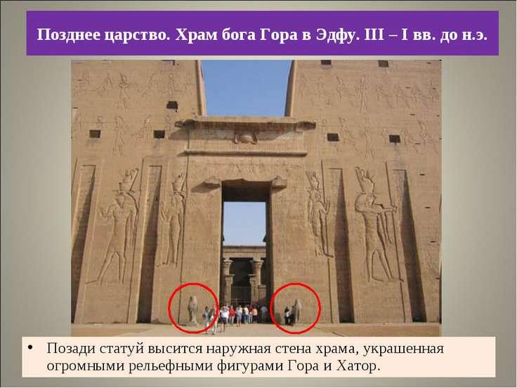 Позади статуй высится наружная стена храма, украшенная огромными рельефными ф...
