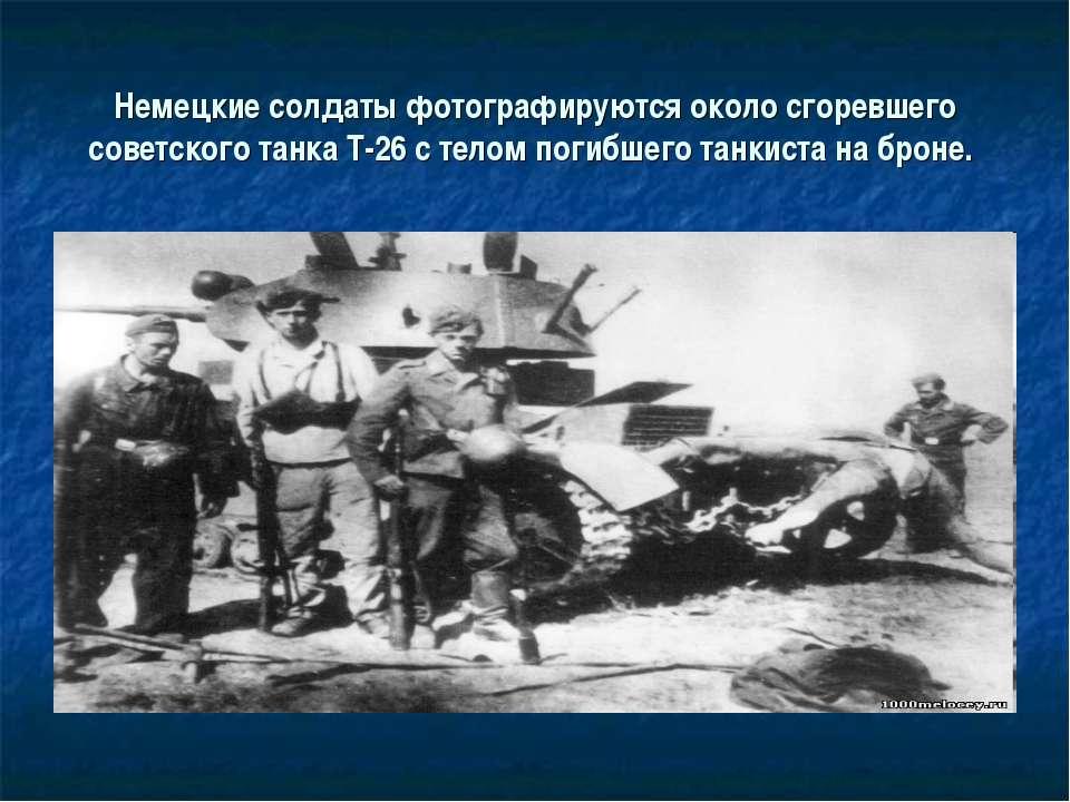Немецкие солдаты фотографируются около сгоревшего советского танка Т-26 с тел...